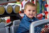 Cute toddler boy riding a car on a merry-go-round and smiling