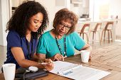 Female healthcare worker filling in a form with a senior woman during a home health visit poster