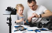 Family Time: Dad And Daughter Repair The Rc Radio Controlled Buggy Car Model And Lead A Video Blog. poster