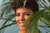 Beautiful young woman with nude makeup looking trought palm leaves. Brazilian smiling woman looking  poster