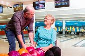 Happy mature couple looking at each other enjoying indoor games poster
