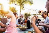 Happy Family Doing A Dinner During Sunset Time Outdoor - Group Of Diverse Friends Having Fun Dining  poster