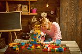 Building Concept. Mother And Son Play With Building Blocks. Mother And Child Build Structure With To poster