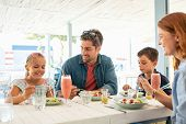 Cheerful family in restaurant enjoying lunch together in a patio. Smiling mother and father with two poster