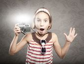 little girl holding  a vintage camera with flash bulb flashing