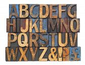 English alphabet with punctuation symbols  in vintage letterpress wood type blocks stained by blue, red and black ink, isolated on white