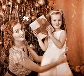 Child with mother receiving gifts under Christmas tree. Black and white retro.