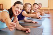 Happy senior woman in fitness class in a health club holding her thumbs up