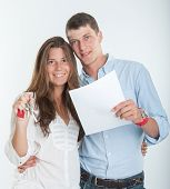 Young couple holding a document and a bunch of keys