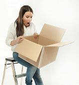 Young woman sitting on a ladder looking at an open cardboard box with a surprised expression