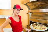 Woman pushing with pizza shovel the pizza in the oven for baking