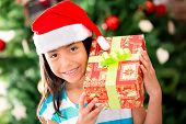 Little girl with a Christmas gift looking happy