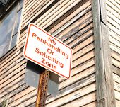 pic of soliciting  - no panhandling or soliciting zone sign near wooden building - JPG