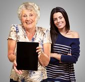 Senior Woman Holding Digital Table In Front Of Young Woman Isolated On Grey Background