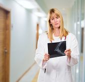 serious doctor looking at an x-ray in a passageway, indoor