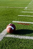 foto of football field  - A brown leather American football on a green football field - JPG