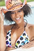 A beautiful sexy young African American girl or young woman wearing a bikini and straw cowboy hat la