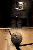 picture of basketball  - Basketball on court with hoop in the background