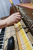 stock photo of tuning fork  - Detailed view of Upright Piano during tuning.Technician hand adjusting the strings of the piano.