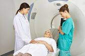 Doctor and MTA talking with patient on MRI machine in radiology in a hospital