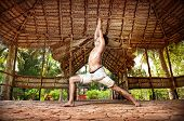 stock photo of virabhadrasana  - Yoga virabhadrasana I warrior pose by fit man in white trousers on the drought earth in yoga shala Varkala Kerala India - JPG