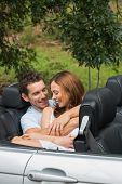 Cute couple cuddling in the backseat of convertible and chatting
