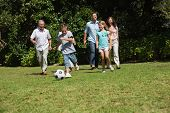 stock photo of multi-generation  - Happy multi generation family playing football together in the park - JPG