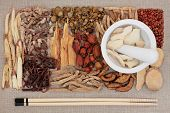 Chinese herbal medicine ingredients with chopsticks and mortar with pestle over hessian background.