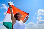 young beautiful cheerful woman holding italian flag against summer blue sky, with love to homeland