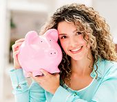Woman holding a piggybank and looking very happy