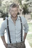 stock photo of suspenders  - Outdoor portrait of a confident sexy young man - JPG
