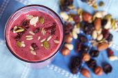 Glass of berries smoothie topped with dried fruits and nuts, blue cloth towel