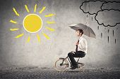 young businessman rides a bike with umbrella