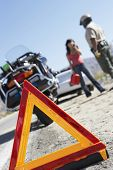 Closeup of a warning triangle sign with police and woman on call by motorcycle and stopped car
