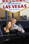 Happy couple in limousine with champagne flutes in front of welcome to Las Vegas sign
