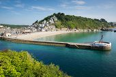 stock photo of west village  - Looe harbour Cornwall England with blue sea on a sunny summer day - JPG