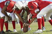 stock photo of huddle  - American football players in a huddle around the ball on field - JPG
