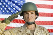 pic of military personnel  - Closeup portrait of a male soldier saluting in front of United States flag - JPG