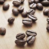 closeup of a pile of roasted coffee beans on a wooden table