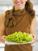 Closeup no prato com um ramo de uvas na mão da jovem a sorrir