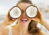 Smiling Young Woman Holding Two Pieces Of Coconut In Front Of Ey
