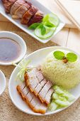 Siu Yuk or crispy roasted belly pork Chinese style and roast duck, served with steamed rice. Singapo