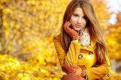 stock photo of cheer-up  - Young woman with autumn leaves in hand and fall yellow maple garden background - JPG