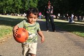 A Young Asian Or Indian Toddler Running With A Red Ball In Hand On A Road Alongside A Green Grass Of