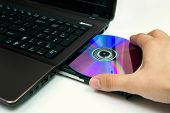Man Insert Compact Disc to Laptop