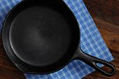 Vintage cast iron skillet with checkered kitchen towel on rustic wood background.  Low key still lif