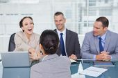 Business team interviewing young applicant in bright office