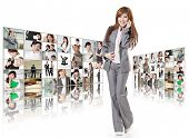 Cheerful business woman talk on phone and stand in front of tv wall, concept about business, teamwor