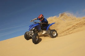 picture of four-wheelers  - Low angle view of a man riding quad bike in desert against the blue sky - JPG