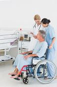 Side view of a doctor talking to a male patient in wheelchair at the hospital